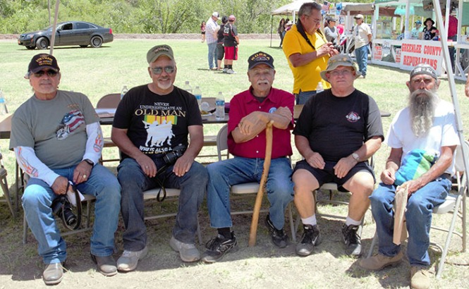 Oscar Urrea, Robert Cisneros, Ismael Ortega and two other veterans enjoy some shade during the festivities at Riverside Park. (Photo by Selena Makrides)