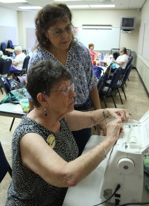 Martha Kasapis, sitting, and Cathy Giancaspro, standing, replace thread in the sewing machine donated to the group. (Photo by Hannah Dickens)
